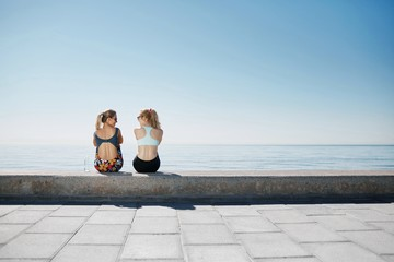 Two girls sitting on the beach after running