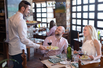 Fototapeta Waiter with restaurant guests at table obraz