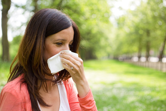 young woman blowing her nose in the park