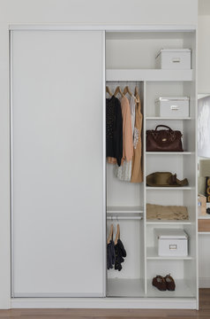 white closet with clothes and accessories