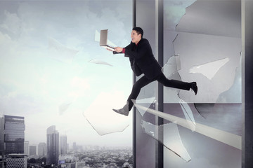 Man with laptop jump through office building window