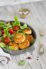 chicken cutlet with fresh vegetable salad in a vintage pan