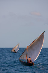 dhow traditional sailing vessel with fisherman heading out into a big blue ocean