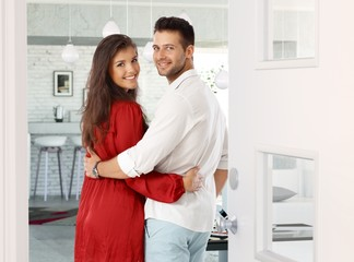 Attractive couple embracing at home