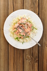 Salmon with rice, scallion and cilantro in white plate on wooden