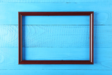 Wooden frame on blue wooden background