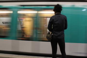 Una ragazza di colore ripresa di spalle aspetta la metropolitana
