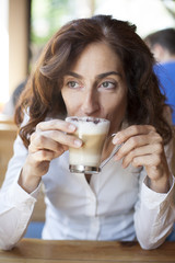 woman drinking cappuccino coffee