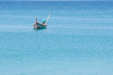 Small fishing boat floating in the sea in sunny day
