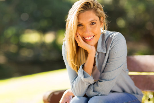 blonde woman sitting on a bench outdoors