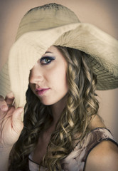 Pretty young woman with big hat pulled over one eye.
