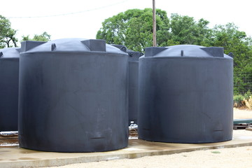 Water tanks holding rain water sit on a concrete slab.