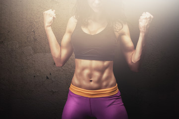 Young fitness model posing with contracted muscles and amazing abs