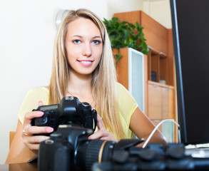 Smiling girl working with photocamera