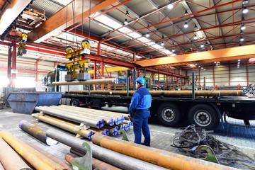 Industriehalle, Arbeiter bedient Kran - Verladung von Stahl