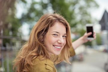 junge frau fotografiert sich mit ihrem handy in der stadt