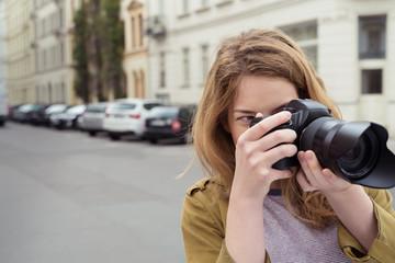 junge fotografin macht ein bild auf der straße