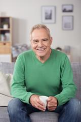 senior sitzt entspannt auf dem sofa in seiner wohnung
