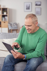 moderner senior tippt auf seinem tablet-pc