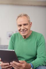 lächelnder senior mit tablet-pc in seiner wohnung