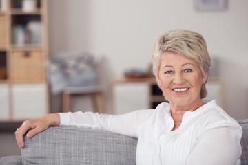 gesunde, vitale best-agerin sitzt entspannt in ihrer wohnung