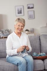lächelnde, moderne seniorin mit strickzeug zu hause