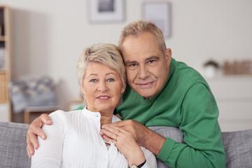 glückliches, älteres paar umarmt sich auf dem sofa