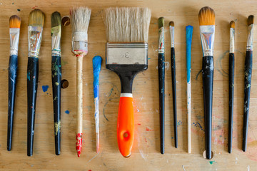 Brushes in different sizes in a Atelier in Hamburg Altona. Close-up in the studio. Tools to mix colors are available. Acrylic colors and paintbrushes are provided to start painting.