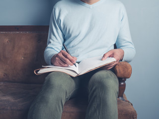 Young man sitting on old sofa writing