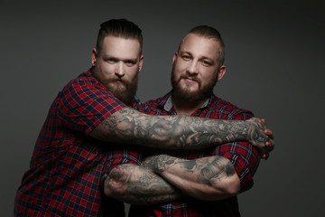 Two guys in red shirts with beards and tattoos.