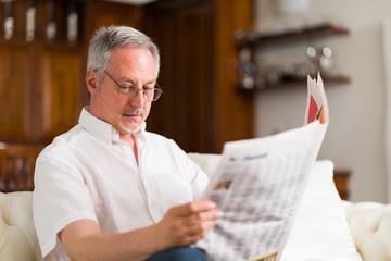 Mature man reading a newspaper