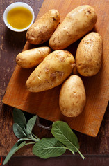 new potatoes on the old wooden background. with sage & olive oil