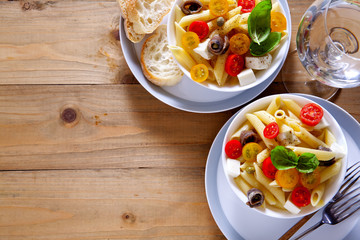 Healthy summer light pasta salad with fresh raw tomatoes, anchov