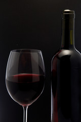 Red wine glass and a bottle in black background
