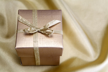 Golden box with ribbon on golden silk