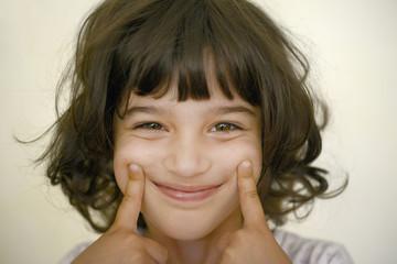 Niña estirándose los labios para mostrar sonrisa