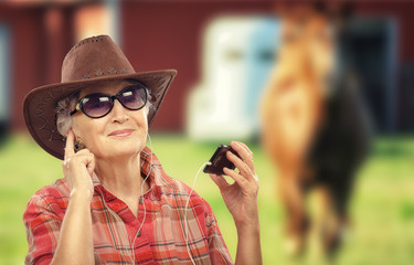Old cowgirl listening music with smart phone