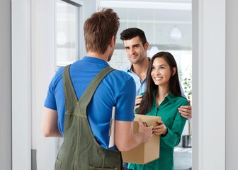 Young couple receiving delivery at home