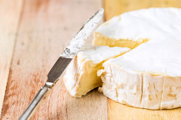 Camembert cheese with cut wedge and vintage knife on wooden tabl