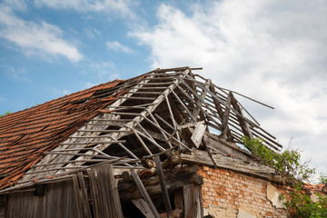 Ruined brick/wooden house - destroyed roof, vegetation.