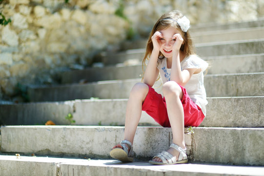 Adorable little girl sitting on stairs