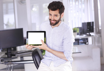 Portrait of young casual businessman sitting at office and holding white screen digital tablet in his hands while looking back and smiling.