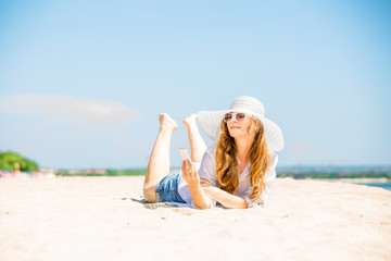 Beautifil young woman lying on the beach at sunny day with phone
