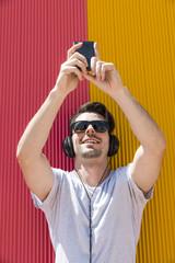 Attractive man with headphones music makes selfie