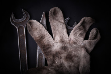 Wrenches and dirty glove on a black background