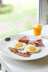 Breakfast with bacon , fried egg and orange juice