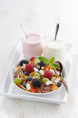 fruit salad and various yoghurt on white wooden table, vertical