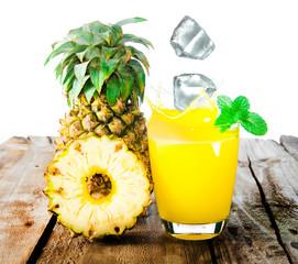 Pineapple and ice with splash on wood