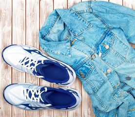 sneakers and denim shirt on a wooden background