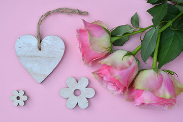 pink painted wooden background with bunch of pink roses and a heart shape photo frame decorated with white wash flowers